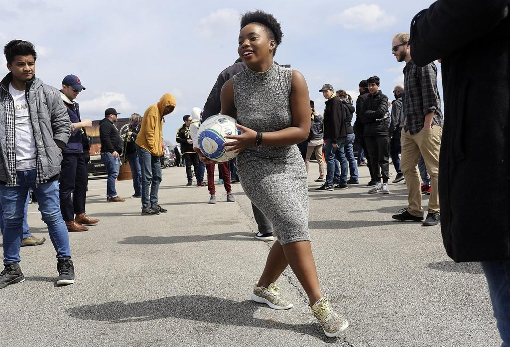 Pascasie Uwase, 16, plays with friends at a tailgate party